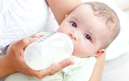 mother bottle feeding baby with formula