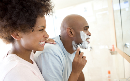 picture of couple looking in the mirror, man is shaving, using shaving foam